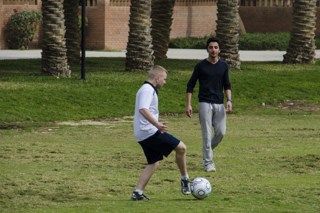 Service members and Kuwaiti students play soccer during a sports day event at the American embassy in Kuwait City, Feb. 16, 2013, as a part of the English Access Micro-scholarship Program. The program is a state department funded, two-year English language program for Kuwaiti youth to not only learn the English language but also learn about American culture as well.