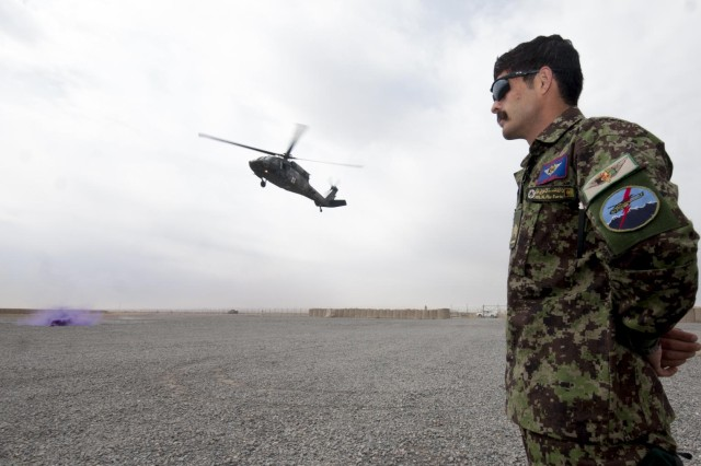 Afghan air force Master Sgt. Abdul Majid Watandoost, the senior medical trainer at the Kandahar Air Wing, watches as a UH-60 Black Hawk helicopter lands at the sling load yard during a simulated casualty evacuation Feb. 13 at Kandahar Airfield, Afghanistan. The simulation was part of the culminating event of a four-week medical evacuation training course administered by Charlie Company, 2nd Battalion, 3rd Aviation Regiment, Task Force Knighthawk.
