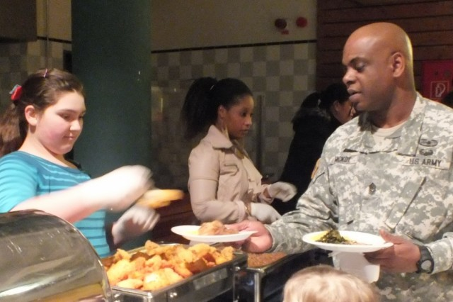 Sixth grader Kaya Arganda serves CSM Kenneth McKoy from a menu that consisted of fried chicken, fish, pork ribs, collard greens, candied yams and more at Hohenfels' National Black History Month celebration, Feb. 22.