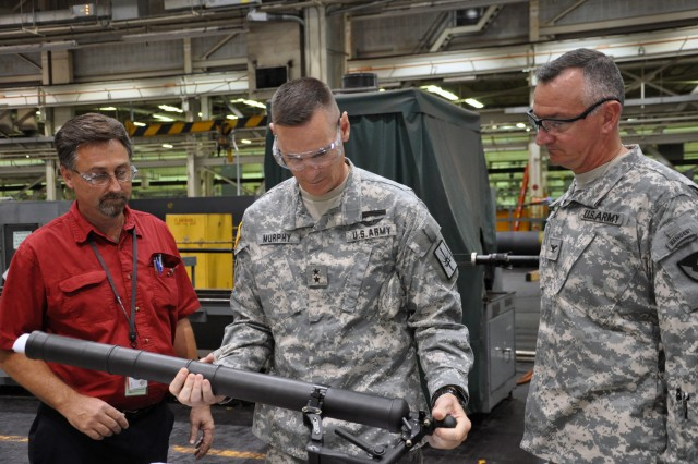 New York State Adjutant General, Maj. Gen. Patrick Murphy, inspects a lightweight 60mm mortar tube.  Arsenal Commander Mark Migaleddi, right, and General Foreman Leon Rosko explain the differences between the lightweight mortar system and the legacy mortar system.