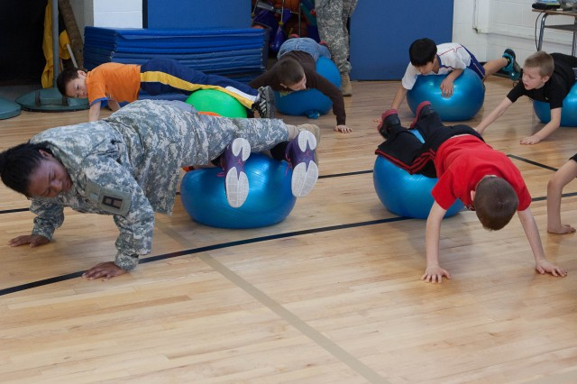 Sgt. 1st Class Lisa O. Cokley, a medic from 2-289th Field Artillery Battalion, 157th Infantry Brigade, demonstrates how to perform an elevated push-up with a ball to fourth grade students at Parkside Elementary School, Columbus, Ind., in an early morning boot camp session. Parkside Elementary is competing to win the Healthy Hoosier School Award for the ninth time, and enlisted the help of its military neighbors from Camp Atterbury Joint Maneuver Training Center, Ind.