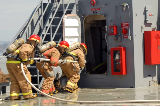"Crew members prepare to fight a simulated fire onboard the LCU 2001 ""Runnymede."" If a fire were to break out, half of the fire team would immediately start spraying down the area of fire while the other half dons fireproof suits. Once half the team is dressed, they switch off positions so they can get dressed while still maintaining constant control of the fire. The crew is expected to take no more than two minutes to be fully dressed in fire protection gear."
