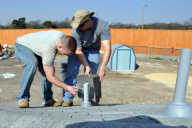 One Soldier spray-paints a ventilation pipe while another shields his work from the wind. This was one of the tasks members of the 401st Military Intelligence Brigade performed while volunteering to help San Antonio Habitat for Humanity Feb. 21.