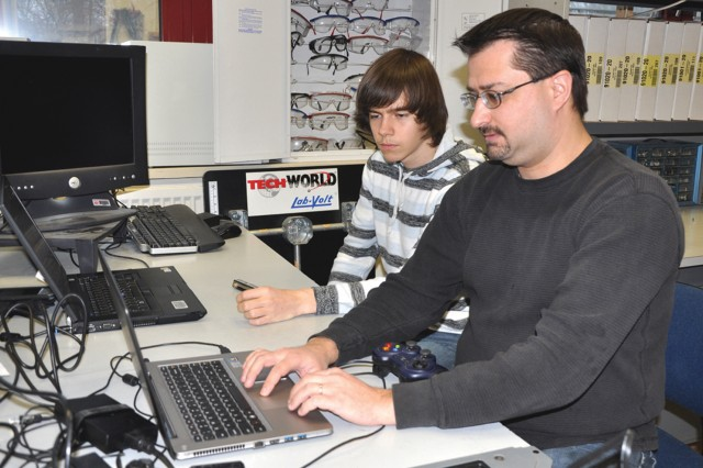 Zachary Cassou works with mentor Brian Barnes on programming Frau Pow 5 in preparation for the stateside competitions.