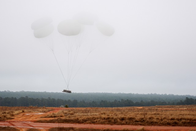 The square silhouette of a heavy drop package containing an engineering vehicle breaks through the cloud ceiling during an airborne operation, Feb. 23. Airmen assigned to 820th RED HORSE Squadron from Nellis Air Force Base, Nev., traveled to Fort Bragg, N.C., to conduct the airborne operation and airfield maintenance training with 161st Engineer Company, 27th Eng. Battalion, 20th Eng. Brigade. Both units will be augmenting 2nd Brigade Combat Team, 82nd Airborne Division for the Joint Operational Access Exercise, Feb. 27-March 9, as well as supporting 2BCT's Global Response Force mission.