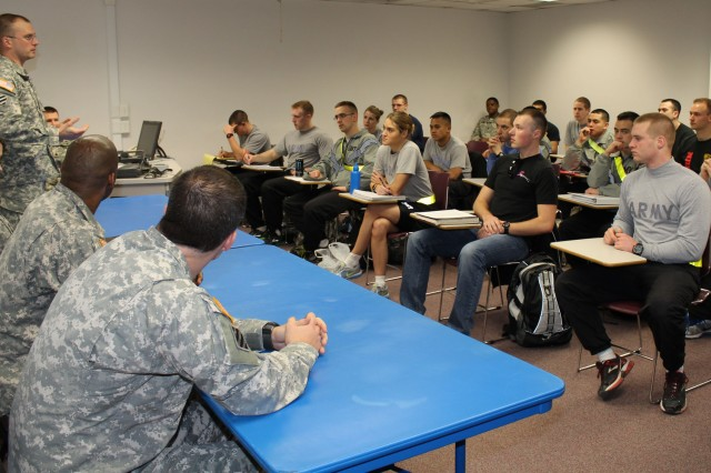 Maj. Jade Miller (standing) discusses his professional background with a class of Northern Illinois University ROTC cadets on Feb. 20, as Majs. Donald Smith, Dwayne Haigler, and Capt. Timothy Godwin look on.
