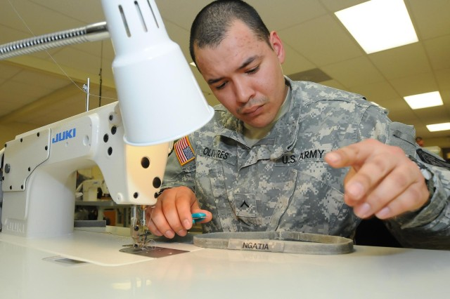 U.S. Army Pvt. Robert Olivares, a laundry, shower and clothing repair specialist, with the 295th Quartermaster Company, 593rd Sustainment Brigade, sews a nametape onto a helmet band at the Clothing and Repair Shop on Joint Base Lewis-McChord, Wash., Feb. 20, 2013. Soldiers at the Clothing and Repair shop sew nametapes, rank and skill identifier badges onto uniforms and TA-50 at no cost to the Soldier. (U.S. Army photo by Sgt. Austan Owen/Released)