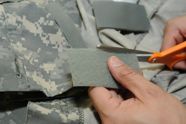 Soldiers with the 295th Quartermaster Company, 593rd Sustainment Brigade, spend the day repairing uniforms and attaching nametapes to anything from cold weather gear to rucksacks. The Clothing and Repair Shop located on Joint Base Lewis-McChord North will attach soldier's nametapes, rank and skill identifier badges on uniforms free of charge. In addition to fixing uniforms, the repair shop will fix Humvee soft-skin doors.