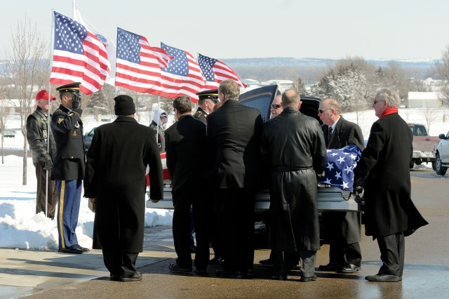 Command Sgt. Maj. Miguel Rivera, 1st Infantry Division senior noncommissioned officer, salutes as pallbearers prepare to carry retired Command Sgt. Maj. Fred Davenport's casket Feb. 22 during a gravesite service at the Kansas Veterans' Cemetery. Davenport passed away Feb. 12 in his Northeast Kansas home. He served several times in the 1st Infantry Division, his last from 1989 to 1994 as the Big Red One's senior noncommissioned officer. He helped lead the division to and from Operation Desert Storm.