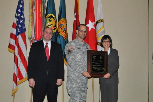 Col. Martin Zybura, 413th CSB commander, accepts the Outstanding Unit/Team Award on behalf of RCO-Hawaii