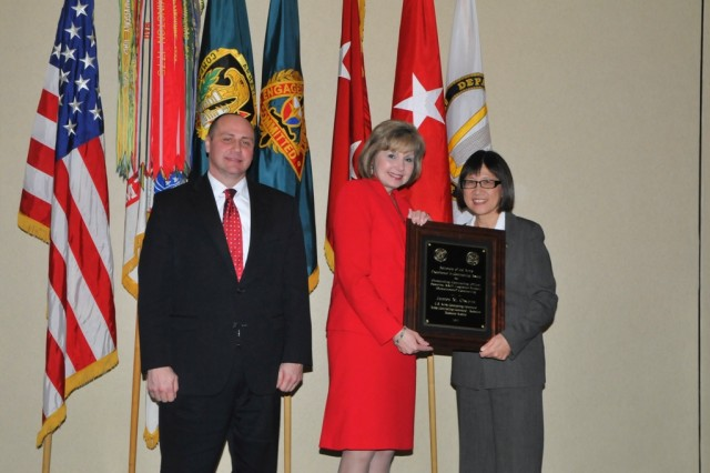 Cathy Dickens, ACC-Redstone director, accepts the Outstanding Contracting Officer Award on behalf of James Owens.