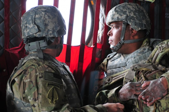 Retired Sgt. 1st Class Jose Mendez and Sgt. Omar Avila gaze out the CH-47 Chinook's porthole window at the Afghan landscape, Feb. 27, 2013, during a return flight to Kandahar Airfield, Afghanistan. Mendez and Avila are visiting several locations in the country with Operation Proper Exit II to speak with soldiers and leave the country on their own terms.