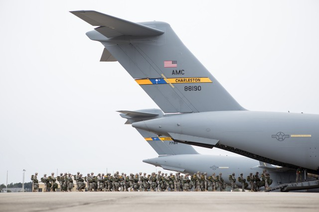 Paratroopers with the 82nd Airborne Division's 1st Brigade Combat Team prepare to board a C-17 Globemaster for a mass-tactical airborne training exercise Feb. 25, 2013, Pope Army Airfield, Fort Bragg, N.C.  Many of the paratroopers are carrying in excess of 100 pounds of gear.  (U.S. Army photo by Sgt. Michael J. MacLeod)