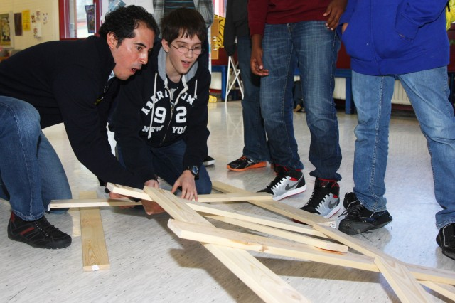 Lawrence Carabajal, a U.S. Army Corps of Engineers Europe District structural engineer, presents bridge building concepts to Wiesbaden Middle School students in honor of National Engineers Week Feb. 21 in Wiesbaden, Germany.