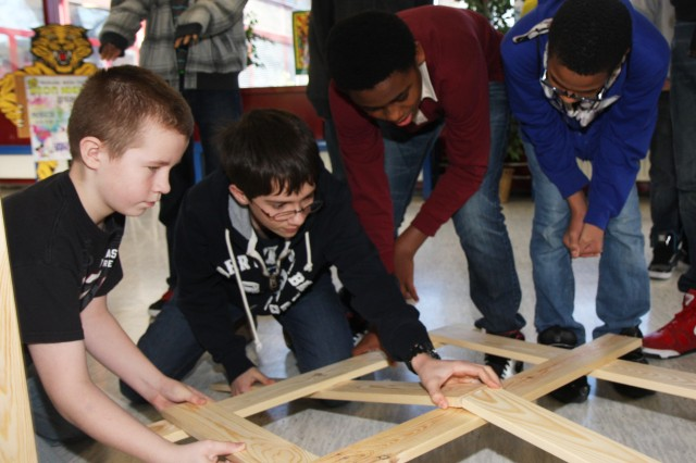 Wiesbaden Middle School students measure, test and build an arch bridge with the help of Lawrence Carabajal, a U.S. Army Corps of Engineers Europe District structural engineer, during National Engineers Week Feb. 21 in Wiesbaden, Germany.