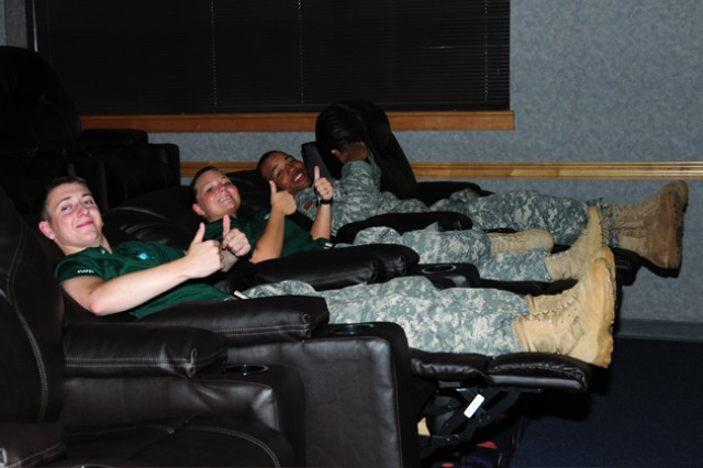 Then Pfc. Alexander Douglas, A Co., 1st Bn., 11th Avn. Regt., Spc. Amber Atkinson, A. Co., 1st Bn., 11th Avn. Regt., and Pfc. Stephon Griffon, B Co., 1st Bn., 13th Avn. Regt., test out the lounging capabilities of the chairs in the movie theater of the renovated BOSS facility during the grand opening last year.