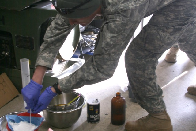 FORT CARSON, Colo. -- Sgt. Stuart Bowman, 663rd Ordnance Company, 242nd Explosive Ordnance Disposal Battalion, 71st Ordnance Group (EOD), collects a sample from a simulated homemade explosive lab, Feb. 22.