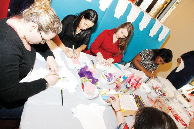 Expectant mothers make decorative baby T-shirts and clothing during a baby shower for expectant mothers at the USO Warrior and Family Center, Feb. 23.