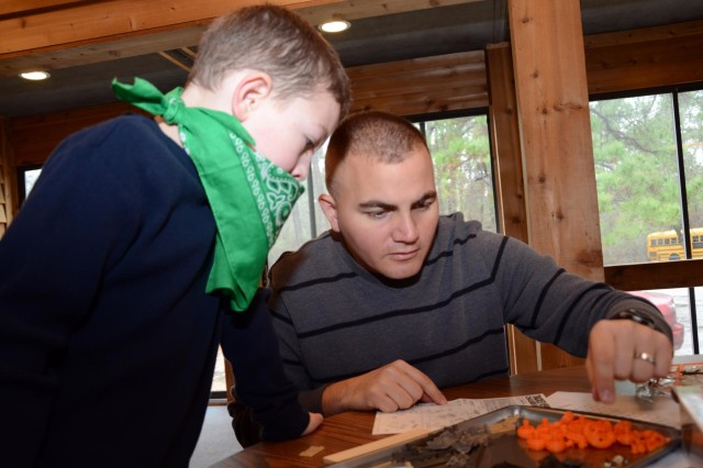 Army 1st Lt. Matthew A. Roll, United States Army Special Operations Aviation Command Assistant Chief of Staff Engineer, and his son, 7-year-old Caleb A. Roll, look over the instructions to build an electric tank during USASOAC's Becoming a Man Adventure at Camp Rockfish, Parkton N.C., Feb. 23, 2013. (U.S. Army photo by Staff Sgt. Thaddius S. Dawkins II, USASOAC Public Affairs)