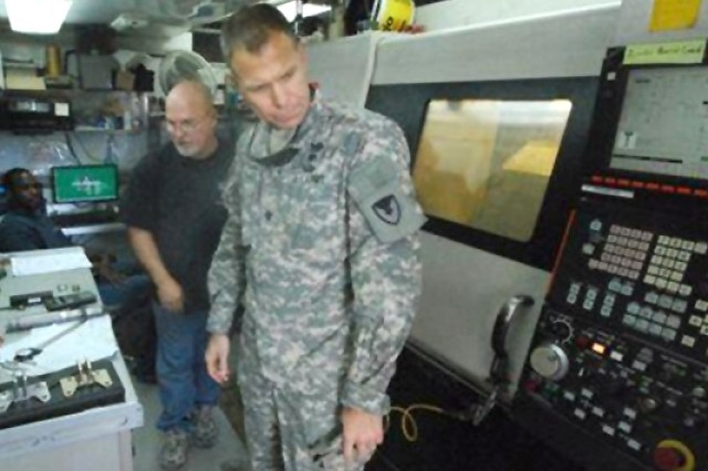 "Joe Westphalen, an Anniston Army Depot employee and the Mobile Parts Hospital lead, briefs Lieutenant Colonel Michael Sauer, commander of the 402nd Army Field Support Battalion "" Southwest Asia, on the MPH's capabilities at Camp Beurhing, Kuwait."