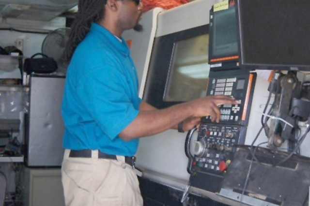 Devan Cowans, an Anniston Army Depot employee and a certified machinist with the Mobile Parts Hospital located at Camp Beurhing, Kuwait, programs a machine to fabricate a Soldier's part request.