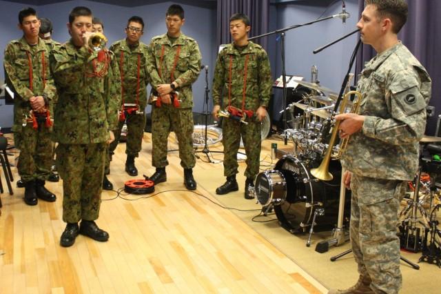 JGSDF LPT Tsubasa Ozawa takes his turn playing a bugle call under the direction of U.S. Army Japan bandsman Sgt. Joshua Tetreault.