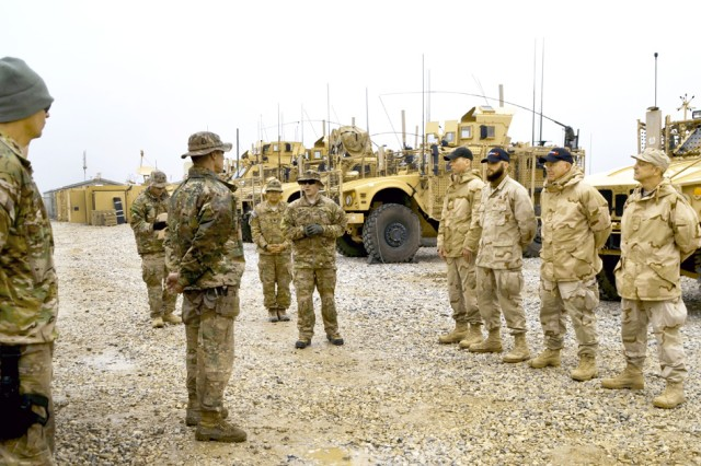 Members of the 1st Squadron, 9th U.S. Cavalry Regiment, known as the 1-9 Cav, (left) stand in formation Feb. 25 during a ceremony at Bagram Air Base, Afghanistan, in which certificates of appreciation were presented to four RDECOM Field Assistance in Science and Technology-Center personnel (right) who  engineered, fabricated and installed force-protection enhancements at a combat outpost. RFAST-C members (from left): engineer Steve Roberts, equipment operator Jon-Luke DeStefano, engineering technician Robert Spetla, and executive officer Dan McGauley.