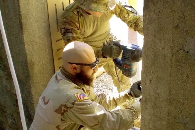 Jon-Luke DeStefano (RFAST-C equipment operator) and Capt. Mitchell Monette (1-9 Cav officer-in-charge of force-protection improvements) work on security infrastructure enhancements at an Army combat outpost in Afghanistan.