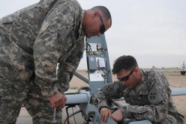 Staff Sgt. John Oehlerking and Spc. John Vance, unmanned aerial system mechanics with Company A, 1st Special Troops Battalion, 1st Brigade Combat Team, 4th Infantry Division, perform pre-flight maintenance checks on an RQ-7B Shadow 200 UAS, at Camp Buehring, Kuwait, Feb. 27, 2013.