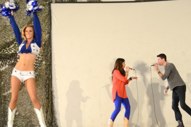 American Idol stars Diana Degarmo and Ace Young sing to the troops while Dallas Cowboys Cheerleader Cassie Trammell dances, at Bagram Airfield, Afghanistan, March 1, 2013. The Diana, Ace and Cassie were participating in a show presented by the United Service Organization.