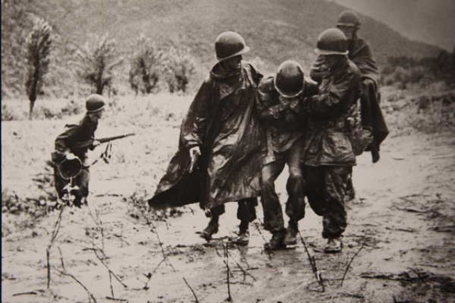 Father Emil Kapaun (right) and a doctor carry an exhausted Soldier off a battlefield in Korea, early in the war.  The photo shows Kapaun to the GI's left. The soldier on the GI's right side was Capt. Jerome A. Dolan, a medical officer with the 8th Cavalry regiment.