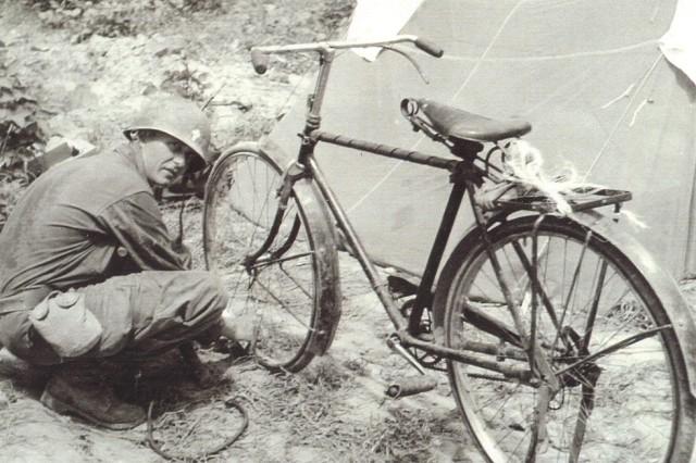 Chaplain Emil Kapaun repairs his bicycle August 11, 1950.