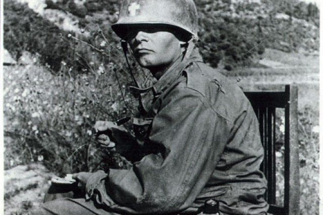 Chaplain Emil Kapaun writes a letter in Korea, circa 1950.  Kapaun spent countless hours writing letters home, both to his family and to the families of fallen soldiers.