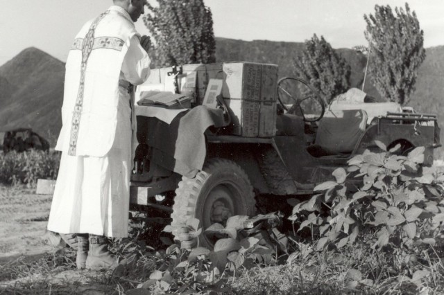 Chaplain Emil Kapaun conducts a field Mass on the hood of his jeep, August 11, 1950.