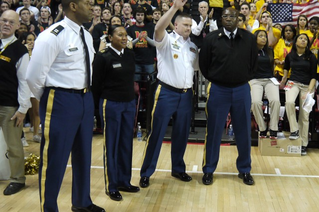 Cpt. John Barbee, Master Sgt. Tomeka Johnson-Nunn, Sgt. 1st Class Jeffery Mooney and Staff Sgt. Shawn Atkinson stand on the University of Maryland's Terrapin's home court during a break between Duke University basketball game as part of a military appreciation celebration on Feb. 16. The 200th Military Police Command Soldiers were honored by the University of Maryland Athletics, in partnership with USO Metro and General Dynamics IT as part of their ongoing efforts to recognize all service members from the Fort Meade, Md., area. (Courtesy photo from the University of Maryland)