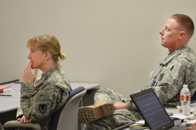 Maj. Julie Stockelman, 407th AFSB operations officer, and Col. Steven Allen, 407th AFSB commander, listen to an instructional brief during a Lean Six Sigma Project Identification and Selection Workshop.