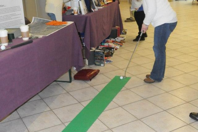 Debbie Strange, wife of Lt. Col. John J. Strange Jr., U.S. Army Garrison Hohenfels commander, practices her putting skills at the Schmidmuehlen Golf and Country Club booth at Hohenfels' Strong Team Expo, Feb