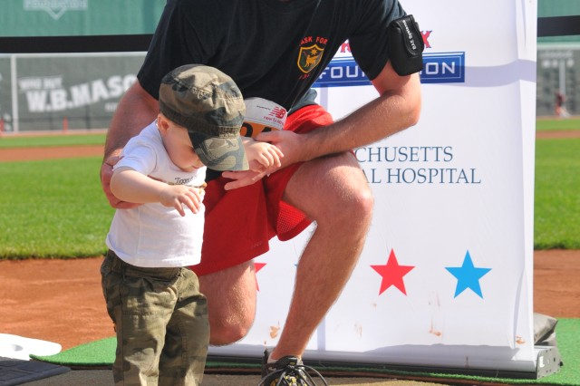 Dan Kemp, a former Soldier and an Operation Iraqi Freedom veteran, helps his son, Ryan, cross home plate after the 2012 Run-Walk to Home Base presented by New Balance at Fenway Park. Kemp, who works at the U.S. Army Research Institute of Environmental Medicine at Natick Soldier Systems Center, will run again this year in the fundraiser for veterans with post-traumatic stress and traumatic brain injuries.