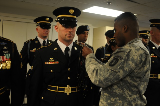Sgt. Rikki Reed, instructor, Regimental Indoctrination Program [RIP], Headquarters and Headquarters Company, 3d U.S. Infantry Regiment (The Old Guard), fastens a buff strap on Spc. James Frenette, supply specialist, Delta Company, 3d U.S. Inf. Regt. (The Old Guard), during a RIP graduation, Feb. 6, on Joint Base Myer-Henderson Hall, Va. RIP, a four-week training program, teaches new Old Guard recruits the high uniform, rifle manual and marching standards of The Old Guard. James's brother, Sgt. Frank Frenette, also serves as a RIP instructor and assisted in his brother's training.  (U.S. Army photo by Sgt. Luisito Brooks)
