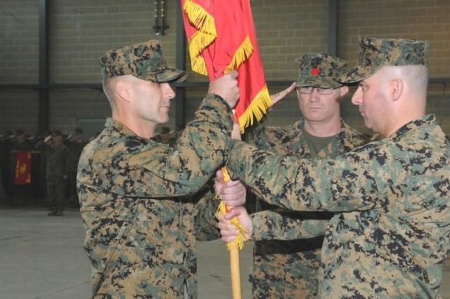 Incoming commander, United States Marine Corps Lt. Col. David Brooks (left) receives the 4th Landing Support Battalion colors from outgoing commander, Lt. Col. Troy Liddi during a change of command ceremony at the Naval and Marine Corps Training Center on Joint Base Lewis-McChord, March 2. The 4th LSB is a Marine Corps Reserve unit that provides command, control and personnel support for helicopter and amphibious landings, and operations that follow ashore. (Photo by Staff Sgt. Mark Miranda)