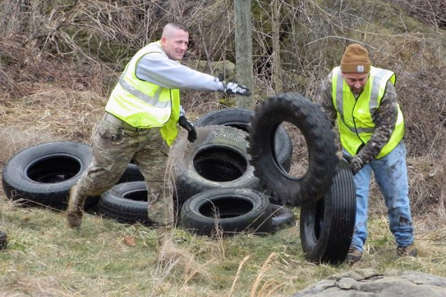 U.S. Army Major Richard Ojeda (left) takes time from a recent day off to help clean up his home community.   He and other members of the LEAD organization spend their weekends cleaning up illegal dump sites around Logan County.  They removed over 244 car and truck tires from this one area that day.
