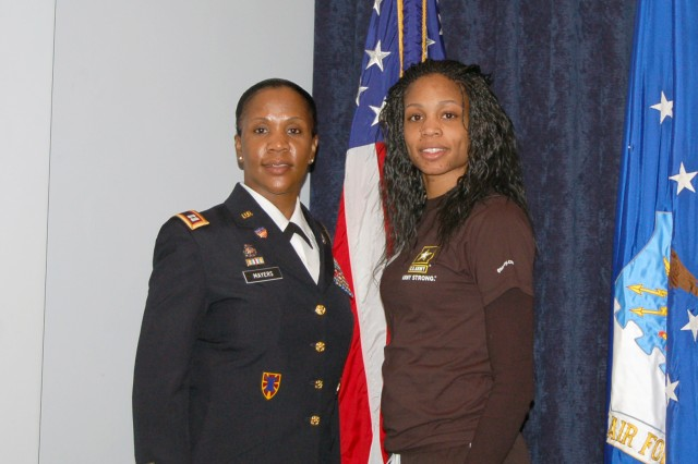 U.S. Army Captain Mia Mayers (left) and her daughter Pvt. 1st. Class TaQuesha Graves pose for photos following Graves' enlistment ceremony where she was sworn into the Army by her mother.
