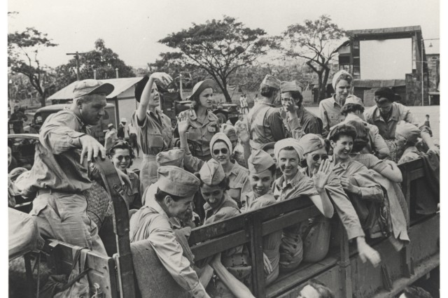 Ruby Bradley, (sitting with her arm over the side rail and waving to the camera) during the liberation of the POW camp at Santo Tomas in the Philippines during World War II.