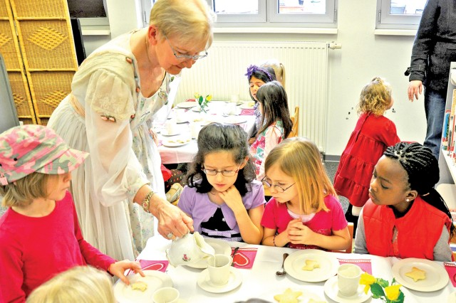 """Grandma Joyce"" Schloesser pours tea for girls during a tea party inspired by ""American Girl"" dolls at the Wiesbaden Library. Schloesser also read the book ""Kirsten's Surprise"" to the girls."