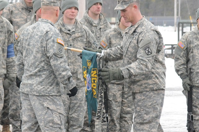Command Sgt. Maj. Jeffrey Dunkelberger, left, and 1st Sgt. Steven Anderson award a drill and ceremony streamer to Warrior Leader Course Class 05-13's 2nd Platoon on Feb. 25 at the NCO Academy campus.