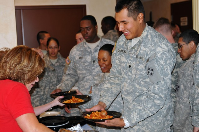 "TRINIDAD, Colo. "" Kim Schultz, consultant for Mt. Carmel Health, Wellness and Community Center, serves dinner to Specialist Andy Carmona, fire direction specialist, Battery B, 3rd Battalion, 16th Field Artillery Regiment, 2nd Brigade Combat Team, 4th Infantry Division, during a meal that the Mt. Carmel in Trinidad, Colo., hosted, Feb. 28, 2013. Mt. Carmel held the dinner to improve the ""Warhorse"" soldiers' resiliency during their month-long training at Pinon Canyon Maneuver Site. (U.S. Army photo by Sgt. Matt Waymire, 2nd BCT PAO, 4th Inf. Div.)"