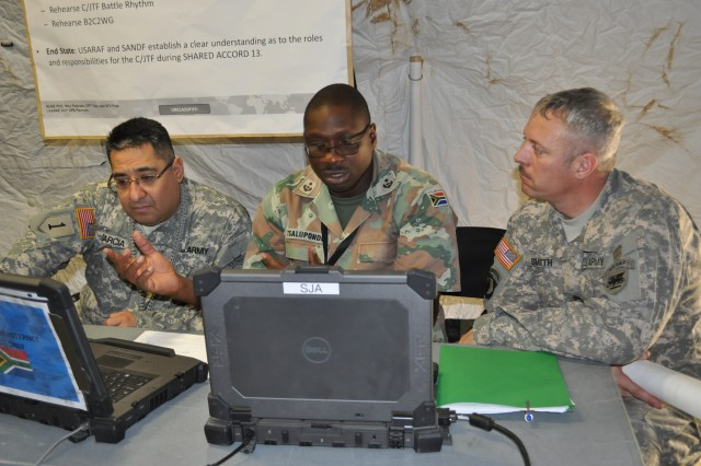 Maj. Albert Garcia and Sgt. 1st Class Jeffrey Smith, of U.S. Army Africa Contingency Command Post, discuss sustainment planning with Lt. Col Light Jongilanga Tsalupondo, administrative commander for the 43rd Brigade of the South African National Defense Force during a contingency command post, or CCP, exercise in preparation for Shared Accord 13, a joint peace keeping and humanitarian exercise. The intent for the CCP exercise was to familiarize the South African National Defense Force with Combined Joint Task Force Headquarters capabilities so U.S. and South African soldiers will have a clear understanding of their roles and responsibilities as a Combined Joint Task Force during Shared Accord 13.