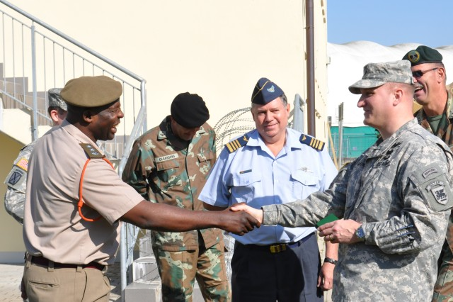 Col.  Stephen Marsh, 43rd Brigade Air Operations commander, South African National Defense Force, presents a unit coin to Lt. Col. Kevin Saatkamp, Deputy Chief of Operations for the U.S. Army Africa Contingency Command Post to award the contingency command post with their efforts to make the exercise a success. The contingency command post exercise was designed to prepare USARAF for Shared Accord 13, a joint peace keeping and humanitarian exercise. The intent for the contingency command post exercise was to familiarize the South African National Defense Force with Combined Joint Task Force Headquarters capabilities so U.S. and South African soldiers will have a clear understanding of their roles and responsibilities as a Combined Joint Task Force during Shared Accord 13.