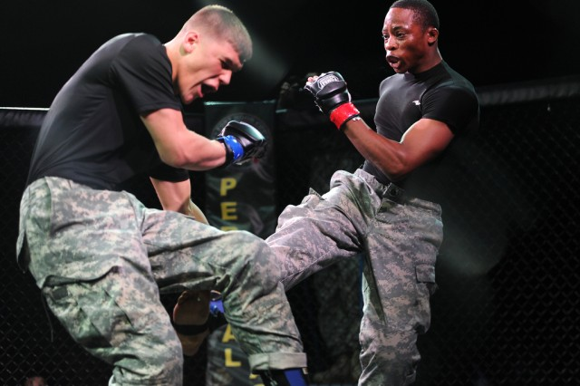Pfc. Lucas Greenwalt (blue), 3rd Cavalry Regiment, and Spc. Adekunle Okusaga (red), 62nd Expeditionary Battalion, fight in the tactical enclosure in the championship bout of the welterweight division during the finals of the 2013 Fort Hood Combatives Tournament Feb. 23 at Abrams Physical Fitness Center at Fort Hood, Texas. Greenwalt won the match by referee stoppage in the first round.