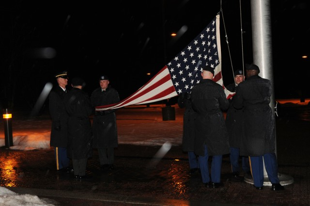 Sgt. Maj. Mitchell DuVall (left), the noncommissioned officer in charge of the flag detail, and Sgt. 1st Class Errick Gordon (right), guide the Soldiers of the flag detail as they raise the 48-star flag at reveille in front of Hays Hall, Feb. 27, 2013.